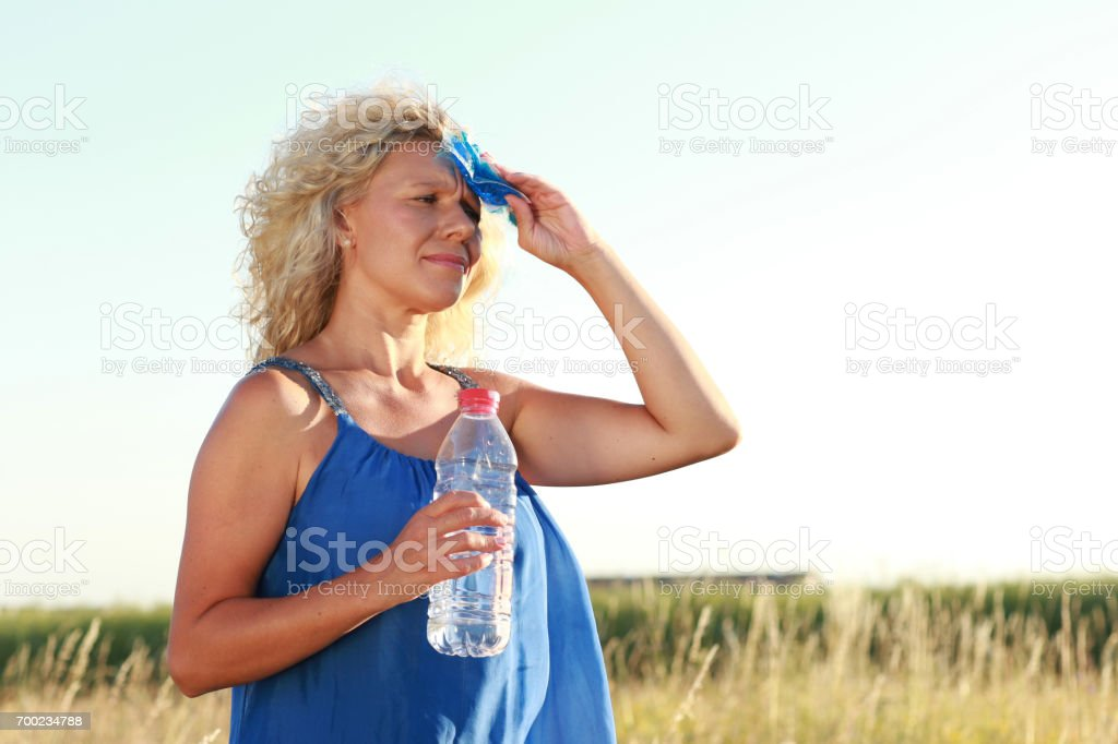 Mature woman with water bottle in summer stock photo