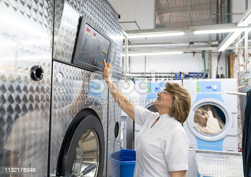 istock Mature woman working at a laundry service operating an industrial washing machine smiling 1132178346