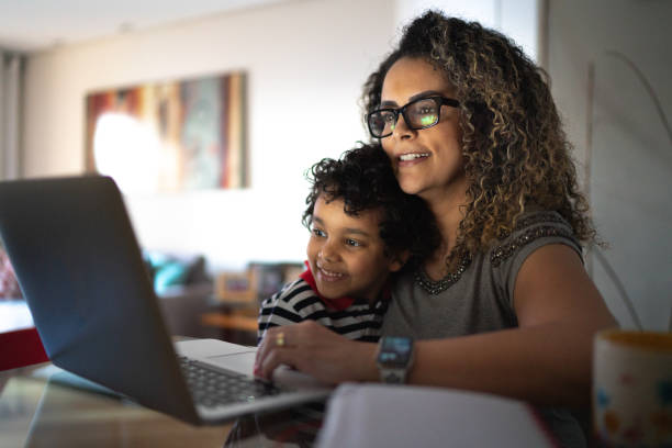 Mature woman working at home, carrying young son stock photo