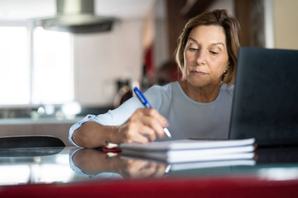 Mature woman working at home Mature woman doing homeoffice adult student stock pictures, royalty-free photos & images