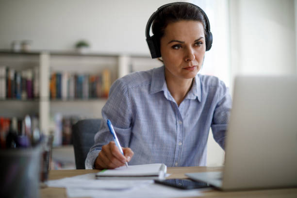 Mature woman working from home during COVID-19 pandemic stock photo