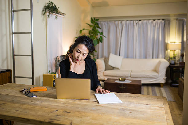 Mature woman working from home Mature woman working from home on her laptop. Kyoto, Japan. December 2016 only japanese stock pictures, royalty-free photos & images