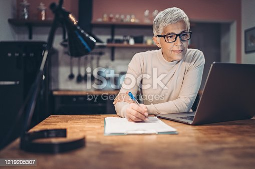 Mature woman working late at home