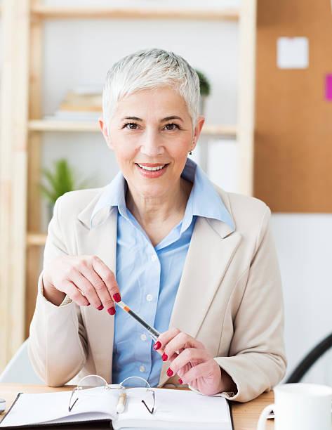 bonito alegre mulher madura no escritório a trabalhar - senior business woman tablet imagens e fotografias de stock