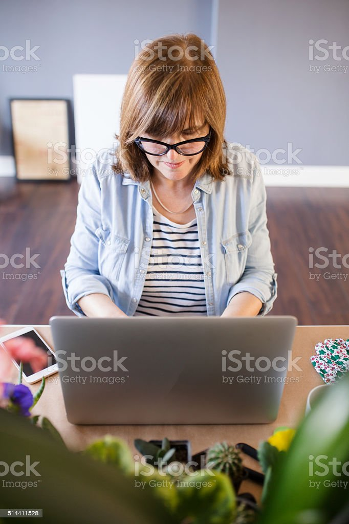 Mature woman working in her home surounded by flowers stock photo