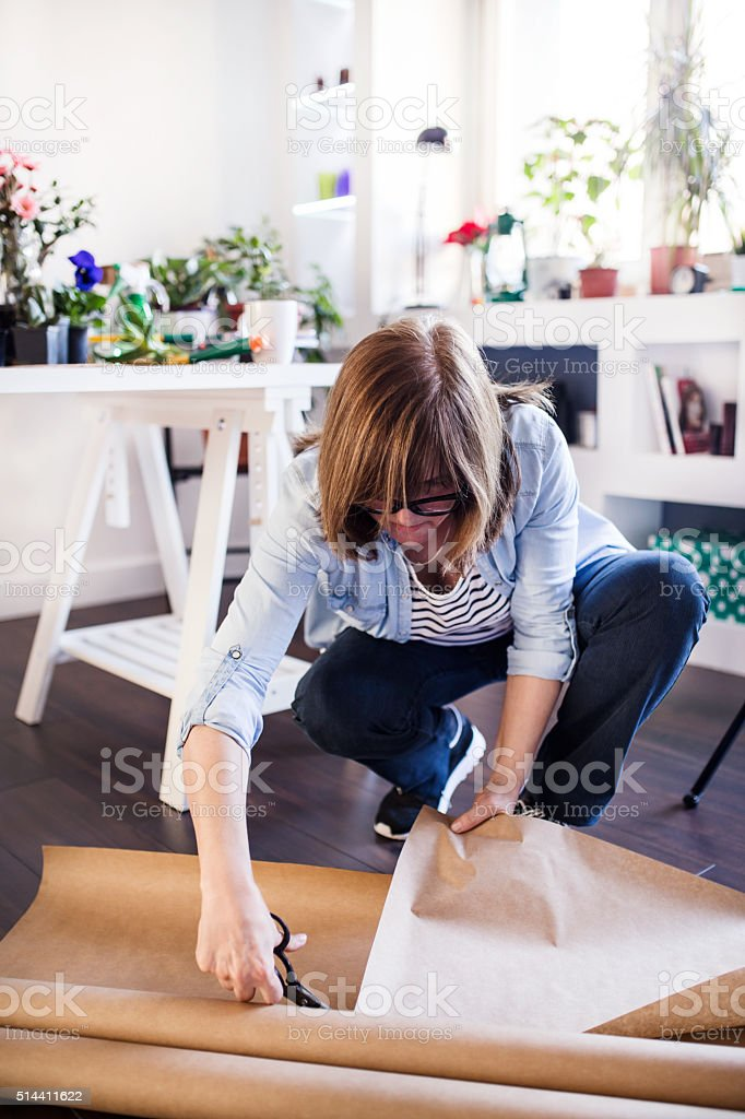 Mature woman working in her office filled with flowers, cutting stock photo