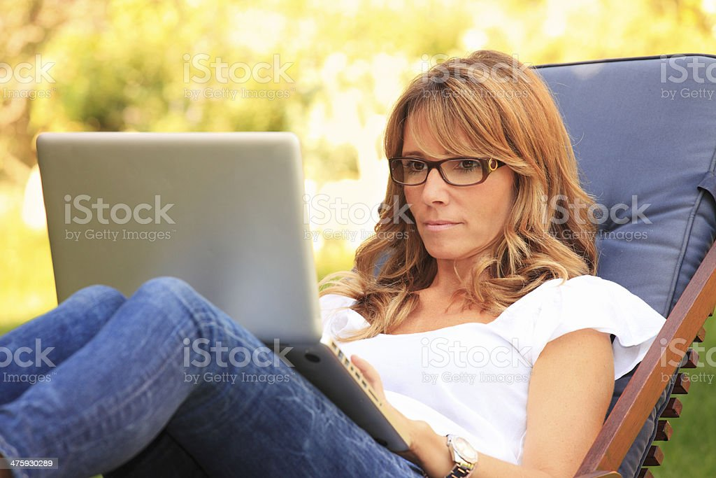 Mature woman working in the garden on her laptop. stock photo