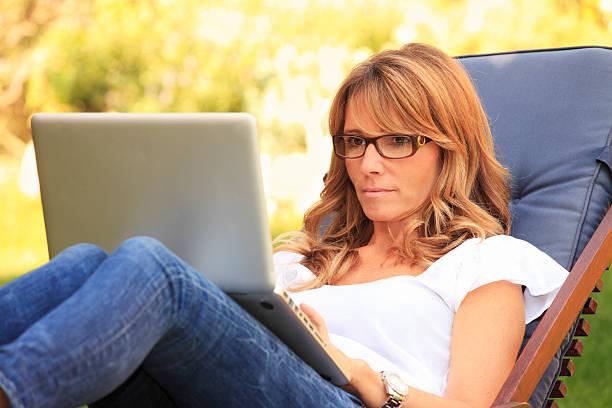 ältere frau, die im garten auf ihrem laptop. - garden types stock-fotos und bilder