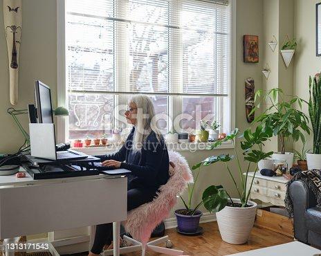 Mujer madura trabajando en la computadora desde casa