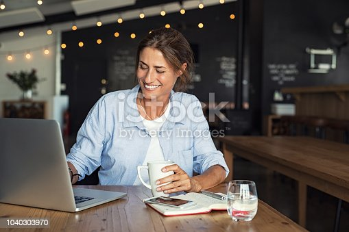 Smiling woman sitting in cafeteria holding coffee mug and working on laptop. Businesswoman checking email on laptop. Beautiful middle aged woman smiling and using laptop at cafe while drinking a cup of tea.