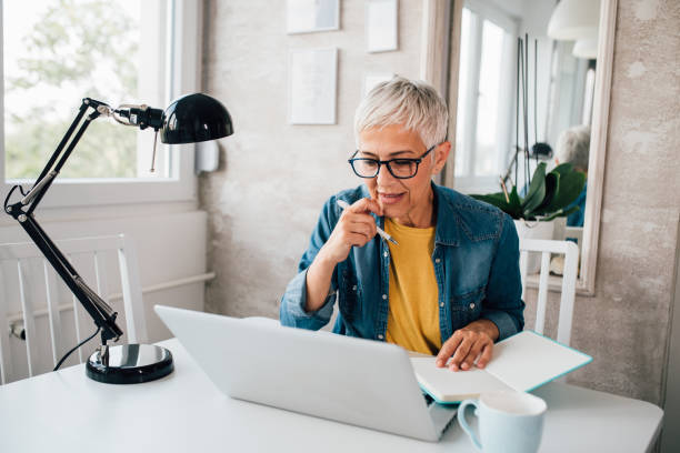 Mature woman working online stock photo