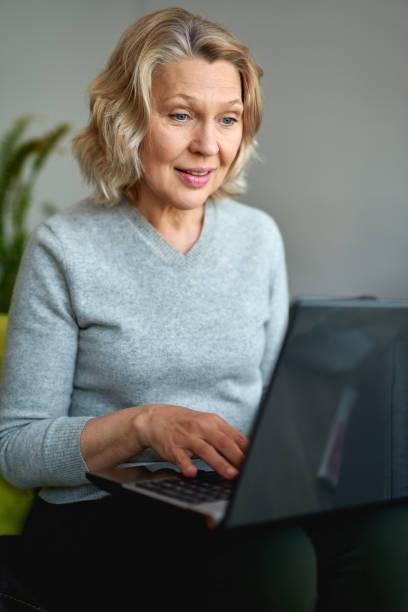 mujer madura trabajando en línea sentado en un sofá en un hogar - foto de stock