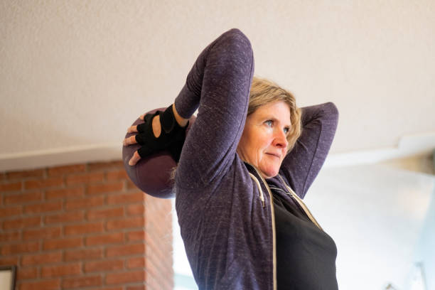 A mature woman working out at home. stock photo