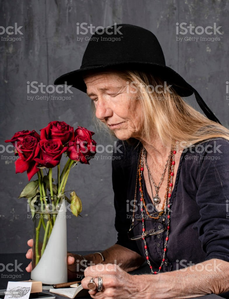Mature woman writes at her desk. She closes her eyes for inspiration or is it prayer? zbiór zdjęć royalty-free