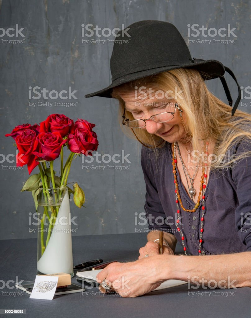 Mature woman writes at her desk. She concentrates on her work. royalty-free stock photo