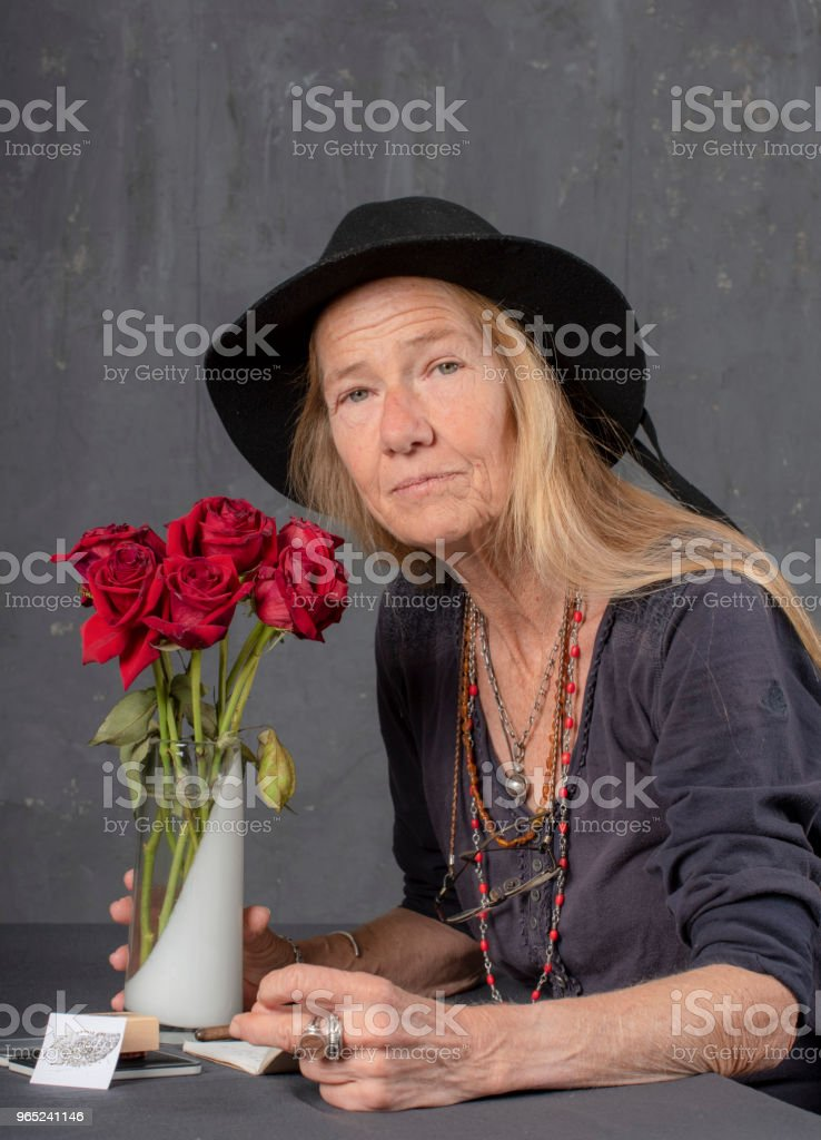 Mature woman writes at her desk. She looks up and smiles at the camera. royalty-free stock photo