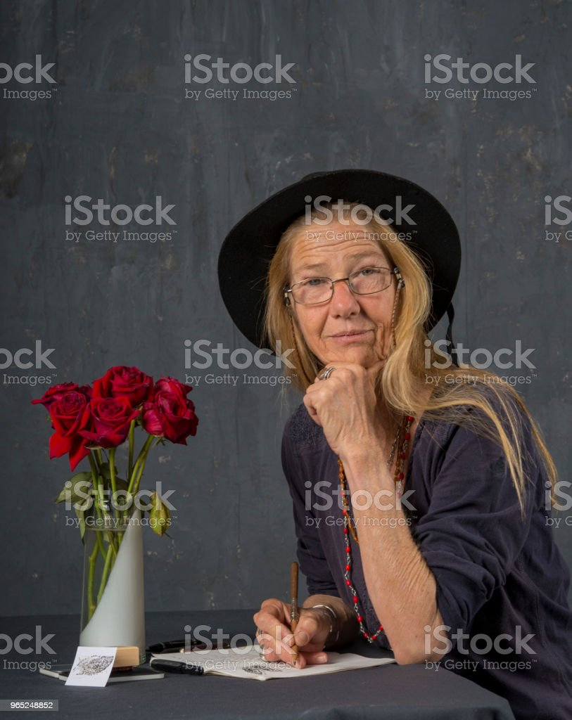 Mature woman writes at her desk. She looks up and smiles at the camera. zbiór zdjęć royalty-free