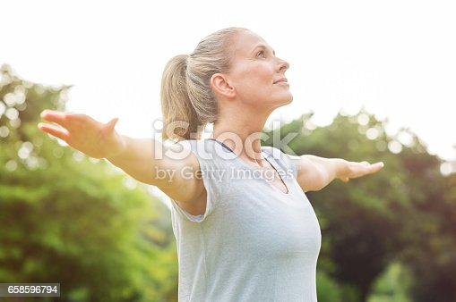 Mature woman doing yoga at park and looking away. Senior blonde woman enjoying nature during a breathing exercise. Portrait of a fitness woman stretching arms and looking away outdoor.