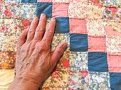 Mature Woman's Hand Smooths a Quilt