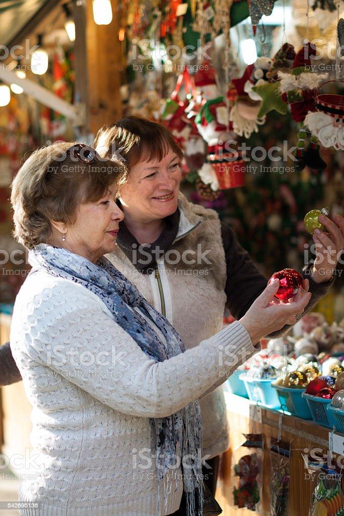 mature women choosing decorations at Christmas market stock photo