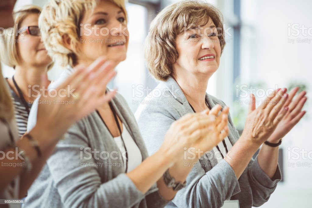 Mature women clapping hands during seminar Businesswomen clapping hands during seminar. Side view. Achievement Stock Photo