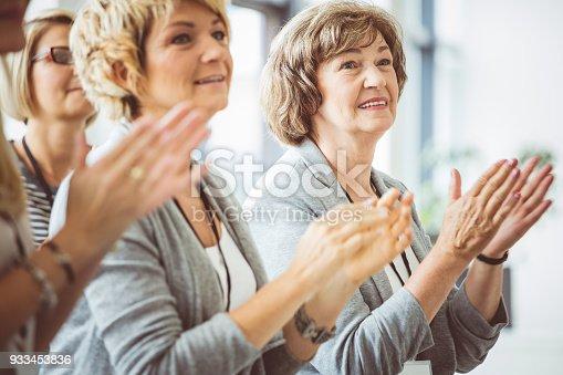 1028234706 istock photo Mature women clapping hands during seminar 933453836