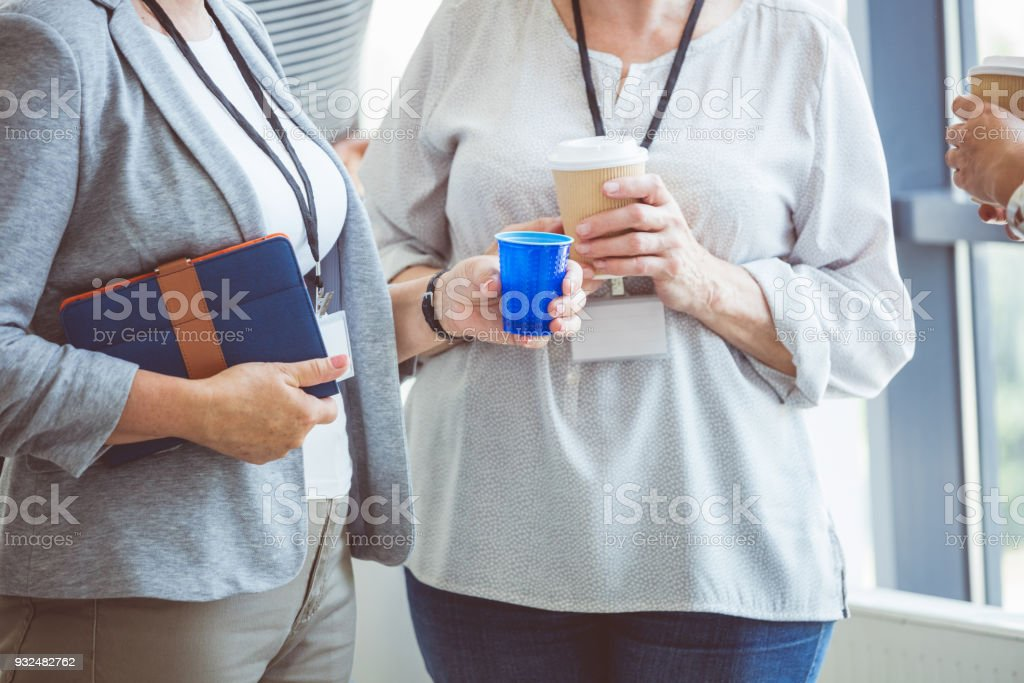 Mature women discussing during coffee break on seminar Mature women discussing during coffee break at conference. Close up of hands, unrecognizable people. Active Seniors Stock Photo