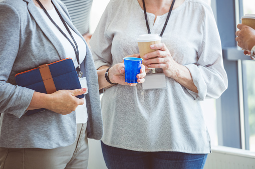 Mature Women Discussing During Coffee Break On Seminar Stock Photo - Download Image Now