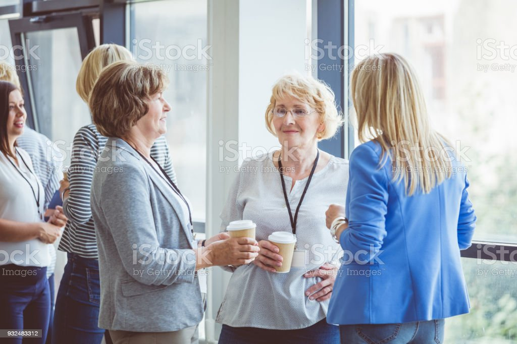 Mature women discussing during coffee break on seminar Women at conference. Group of women discussing during coffee break. Active Seniors Stock Photo