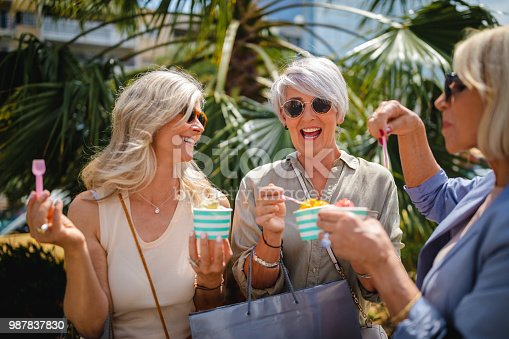 Fashionable senior women eating ice cream and shopping together in the city in summer