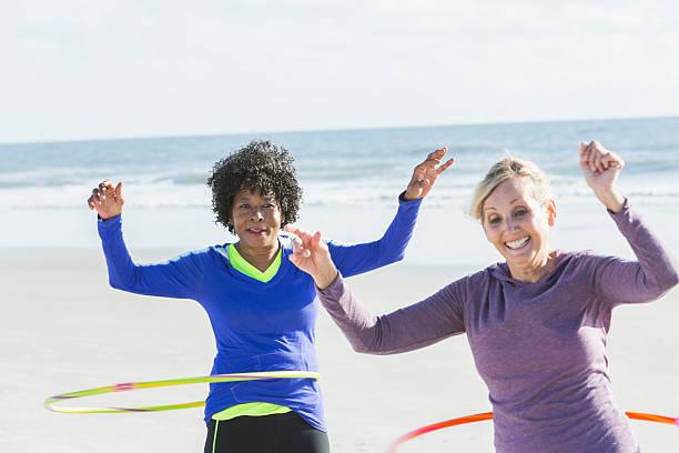 ältere frau training am strand mit seinem hoola reifen - hula hoop workout stock-fotos und bilder