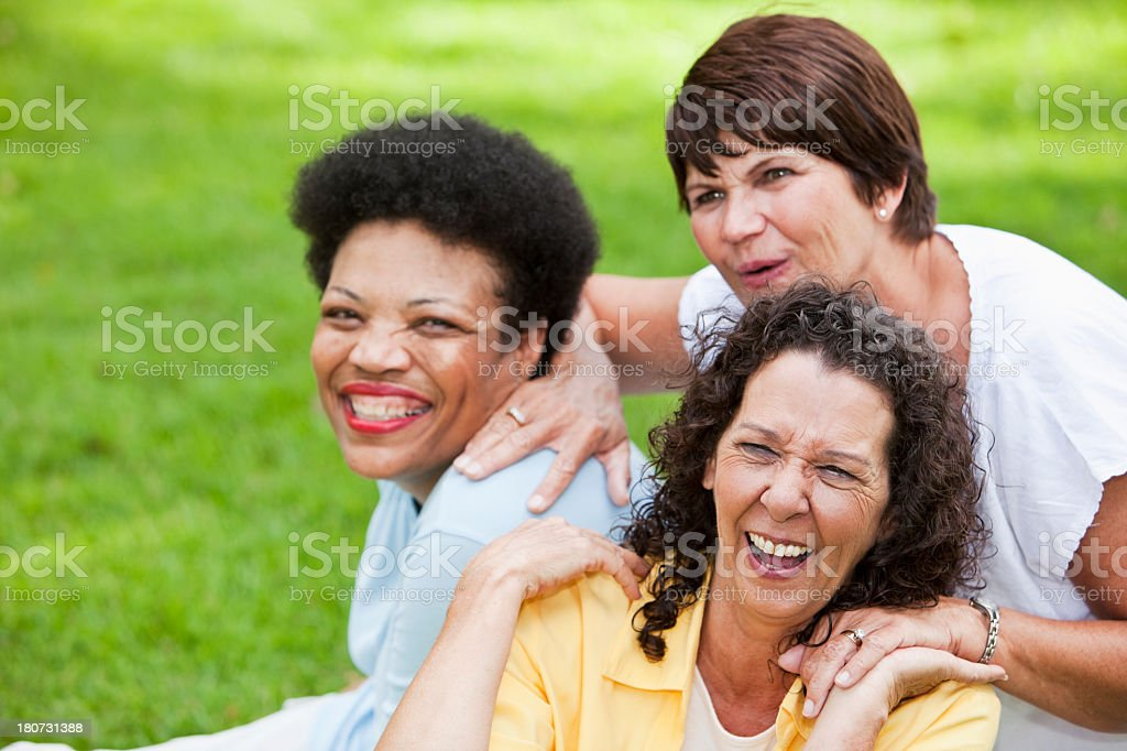Portrait of multi-ethnic mature women outdoors laughing. Focus on...