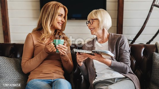Mature women reading book with her daughter drinking coffee at home