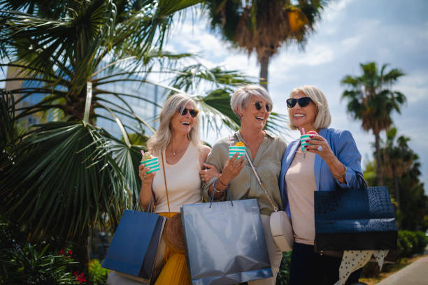 Mature women shopping and eating ice cream in the city Fashionable senior friends having fun doing shopping, eating ice cream and walking in the city wundervisuals stock pictures, royalty-free photos & images