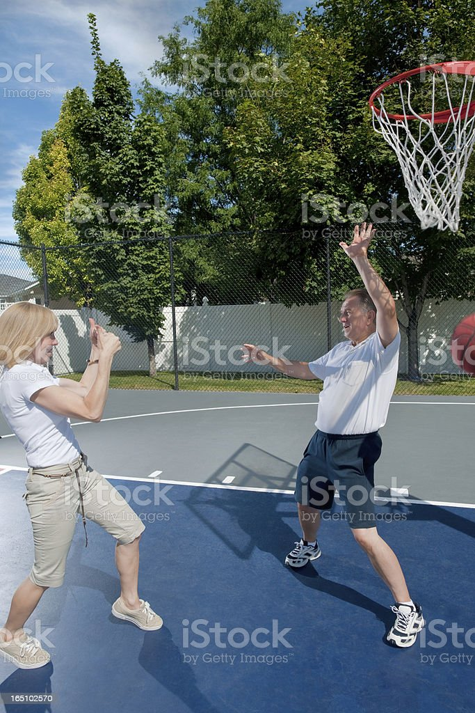 Mature Women Teasing Husband While Playing Basketball stock photo