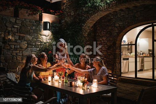 Small group of mature woman are drinking in their holiday villa courtyard at night. They are toasting their glasses.