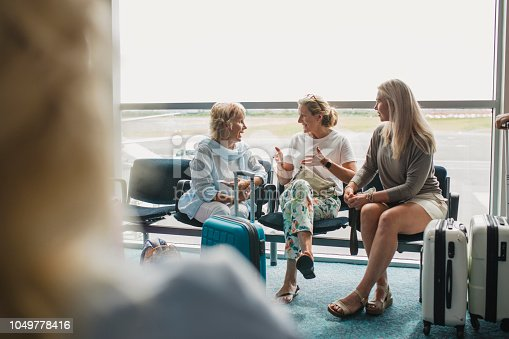 A front view shot of three mature women communicating in an airport departure area, they are wearing nice clothing and are surrounded by suitcases and luggage as they wait to go on vacation.