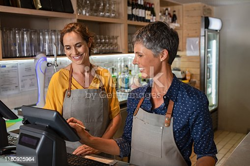 istock Mature women waitress working at coffee shop 1180925964