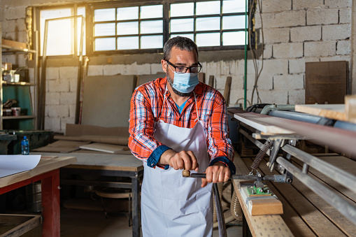 Carpenter cutting plank by circular saw in him workshop