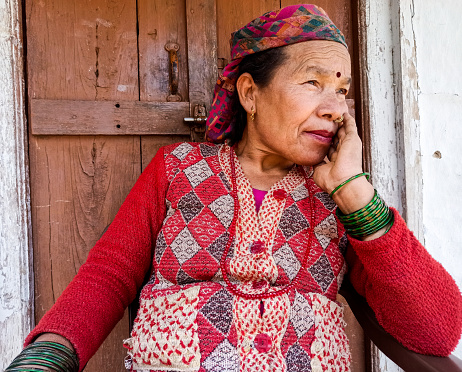 Outdoor image of a mature-adult Asian women holding cheeks. She is looking away and contemplating. image shot is  Himachal Pradesh, India.