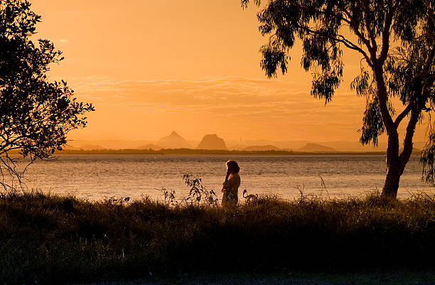 Mature-aged woman alone on the beach at sunset stock photo