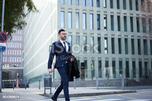 istock Matured male entrepreneur dressed in elegant suit strolling outdoors crossing road in business district of megalopolis, handsome professional economist hurrying for conference feeling confident 904389874