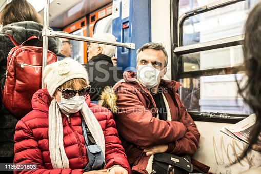 istock Matured man and woman wearing protective mask in train. 1135201603