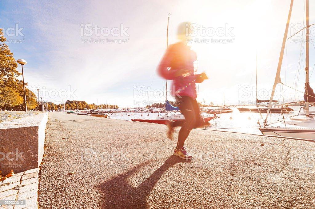 Mature-senior woman jogging beside the sea stock photo