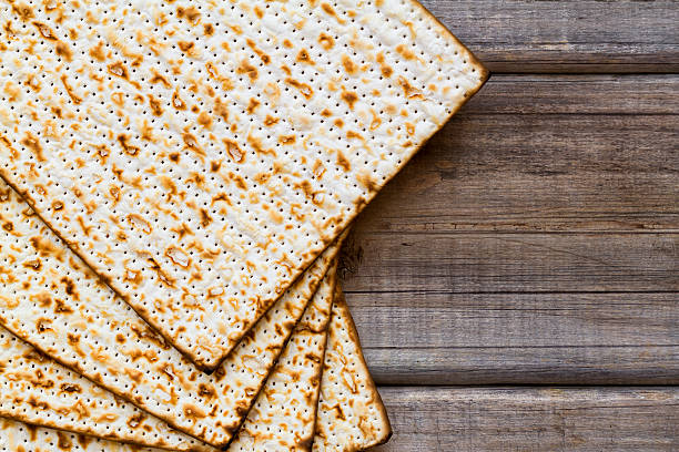 matza on a wood background - passover stock photos and pictures