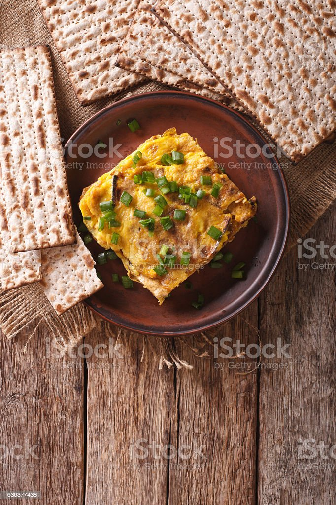 Matzah brei with green onions close-up on a plate. vertical stock photo