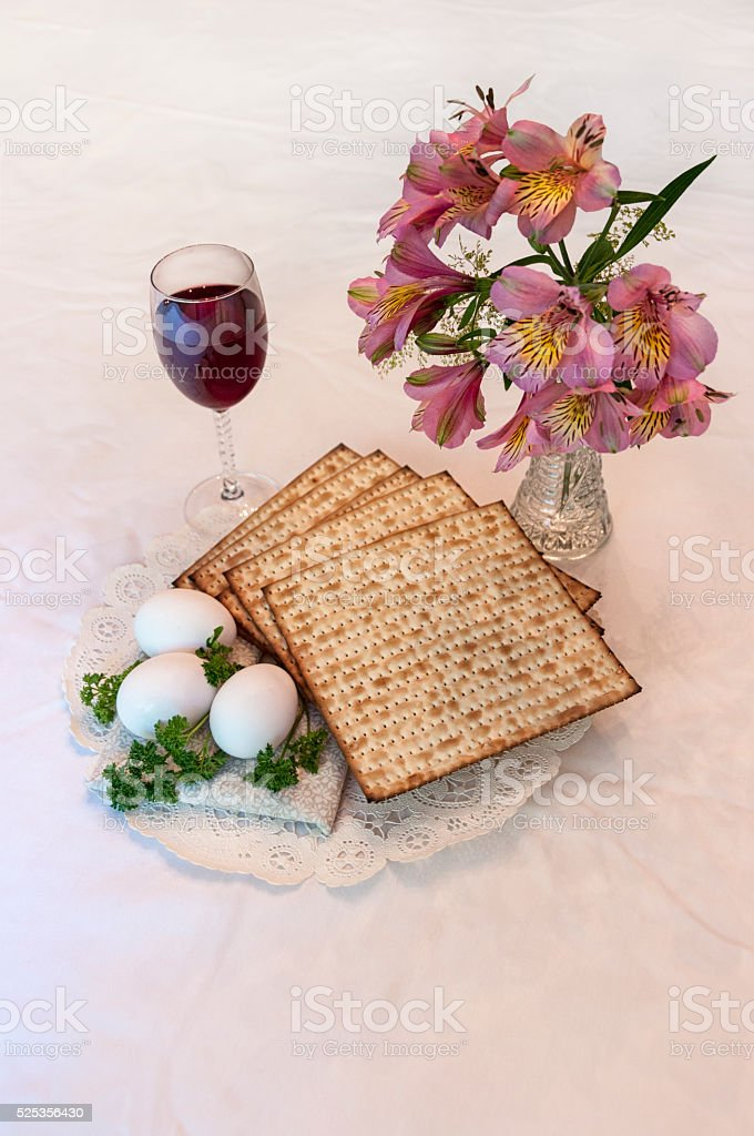 Matzo, red sweet wine, eggs, parseley and flowers stock photo