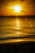 Maui Hawaii Sunset Scenic With Beach, Waves, and Sail Boat.  Bright, sunfilled sunset.  Copy Space.
