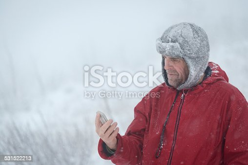 Portrait of a pensive senior man with beard using his smart phone in the mountains, snowing, windy, Alps, Europe.