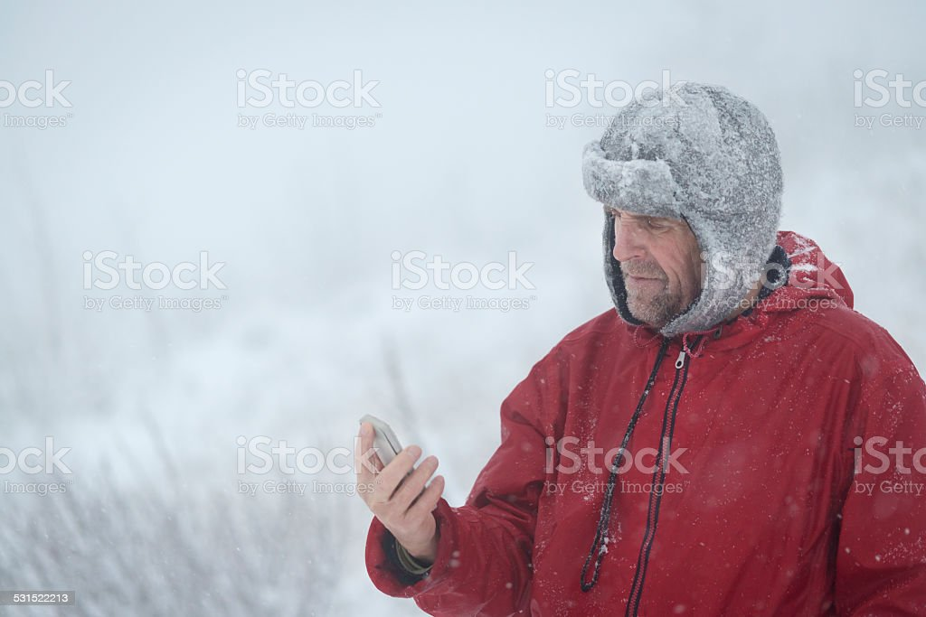 Mauntain Senior Man with Smart Phone, Snowing, Alps, Europe stock photo